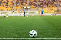 Balón de fútbol en el primero plano y los jugadores borrosos Fotografía de archivo