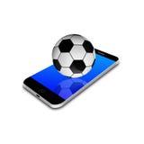 Balón de fútbol en el smartphone, ejemplo del teléfono celular Fotos de archivo libres de regalías