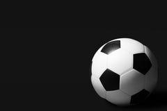 Balón de fútbol en fondo oscuro Foto de archivo