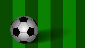 Balón de fútbol en fondo verde Imagen de archivo libre de regalías