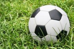 Balón de fútbol en hierba Fotos de archivo