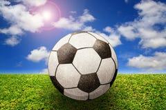 Balón de fútbol en hierba con el cielo Imagenes de archivo