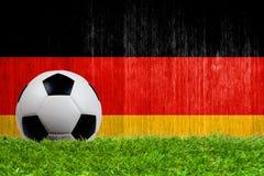 Balón de fútbol en hierba con el fondo de la bandera de Alemania Foto de archivo libre de regalías