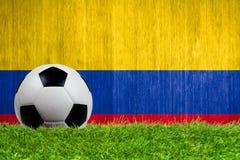 Balón de fútbol en hierba con el fondo de la bandera de Colombia Fotografía de archivo libre de regalías