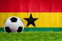 Balón de fútbol en hierba con el fondo de la bandera de Ghana Imagenes de archivo