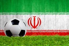 Balón de fútbol en hierba con el fondo de la bandera de Irán Imagenes de archivo