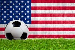 Balón de fútbol en hierba con el fondo de la bandera de los E.E.U.U. Fotos de archivo libres de regalías