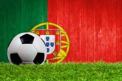 Balón de fútbol en hierba con el fondo de la bandera de Portugal Imagenes de archivo