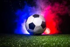 Balón de fútbol en hierba con la bandera de Francia con humo y luces Concepto del fútbol Imagen de archivo