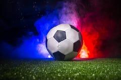 Balón de fútbol en hierba con la bandera de Francia con humo y luces Concepto del fútbol Fotos de archivo