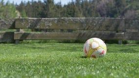 Balón de fútbol en la hierba - cámara lenta del niño que golpea la bola con el pie descalzo en el jardín