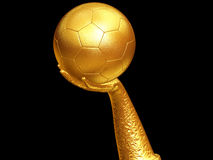 Balón de fútbol en la mano de oro Imagenes de archivo