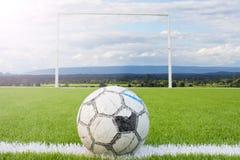 Balón de fútbol en la rejilla blanca w del césped del verde artificial del campo de fútbol Imagen de archivo