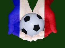 Balón de fútbol en las manos de los colores de la bandera nacional de Francia fotografía de archivo