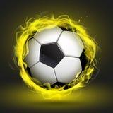 Balón de fútbol en llama amarilla Fotografía de archivo
