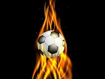 Balón de fútbol en llama ascendente en fondo negro Imagenes de archivo