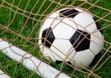 Balón de fútbol en meta Foto de archivo