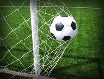 Balón de fútbol en meta Fotos de archivo