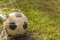 Balón de fútbol en meta con el fondo verde Foto de archivo