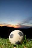 Balón de fútbol en puesta del sol Fotografía de archivo