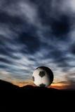 Balón de fútbol en puesta del sol Imagen de archivo