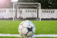 Balón de fútbol en rejilla artificial del blanco del verde del campo de fútbol del césped Fotografía de archivo libre de regalías