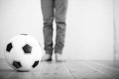 Balón de fútbol en un piso de madera Imágenes de archivo libres de regalías