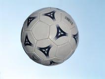 Balón de fútbol en vuelo Imagenes de archivo