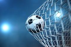 balón de fútbol de la representación 3d en meta Balón de fútbol en red con el fondo ligero del proyector o del estadio, concepto  Imagen de archivo
