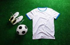 Balón de fútbol, listones y camiseta blanca contra césped artificial imagenes de archivo