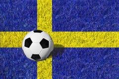 Balón de fútbol o bola del fútbol en el campo azul/del amarillo, bandera nacional de Suecia Imagen de archivo