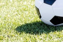 Balón de fútbol que se sienta en hierba en luz del sol Imágenes de archivo libres de regalías