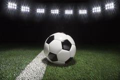 Balón de fútbol tradicional en campo de hierba bajo luces en la noche imagen de archivo libre de regalías