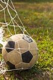 Balón de fútbol viejo en meta Imagen de archivo