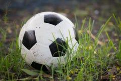 Balón de fútbol viejo estropeado, desinflado levemente, en la hierba larga de la O.N.U Imagen de archivo libre de regalías