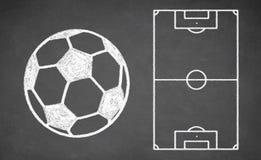 Balón de fútbol y esquema táctico en la pizarra Imágenes de archivo libres de regalías