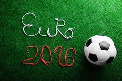 Balón de fútbol y muestra del euro 2016 contra césped artificial Imagen de archivo libre de regalías