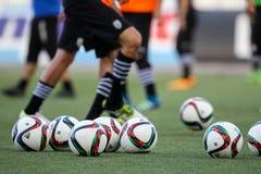 Balón de fútbol y pies de jugadores Fotografía de archivo libre de regalías
