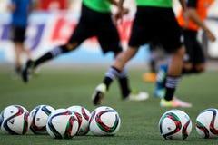 Balón de fútbol y pies de jugadores Imagen de archivo libre de regalías