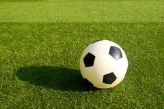 Balón plástico del fútbol o de fútbol en hierba verde Fotos de archivo