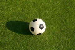 Balón plástico del fútbol o de fútbol en hierba verde Imagen de archivo libre de regalías