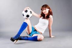 Balón sitted joven de la muchacha y de fútbol Foto de archivo libre de regalías