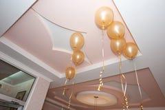Balões amarelos dourados que penduram do teto Imagem de Stock Royalty Free