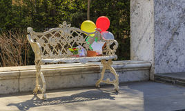 Balões amarrados a um banco velho e às caixas com presentes Imagem de Stock Royalty Free