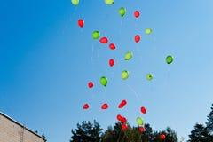 balões As crianças liberaram muitas bolas com cordas no céu Balões vermelhos e verdes Fotografia de Stock Royalty Free