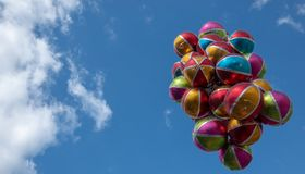 Balões brilhantes coloridos com listras brancas e áreas coloridas na frente de um céu azul quase sem nuvens foto de stock royalty free