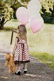 Balões carreg da criança e arrasto de sua peluche Fotografia de Stock Royalty Free