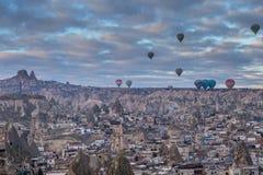 Balões coloridos de voo sobre a cidade da caverna de Goreme, Cappadocia, Turkeyn Fotografia de Stock