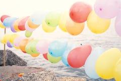 Balões coloridos no fundo do céu azul e do mar imagem de stock