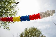 Balões da cor no ar entre árvores Foto de Stock Royalty Free